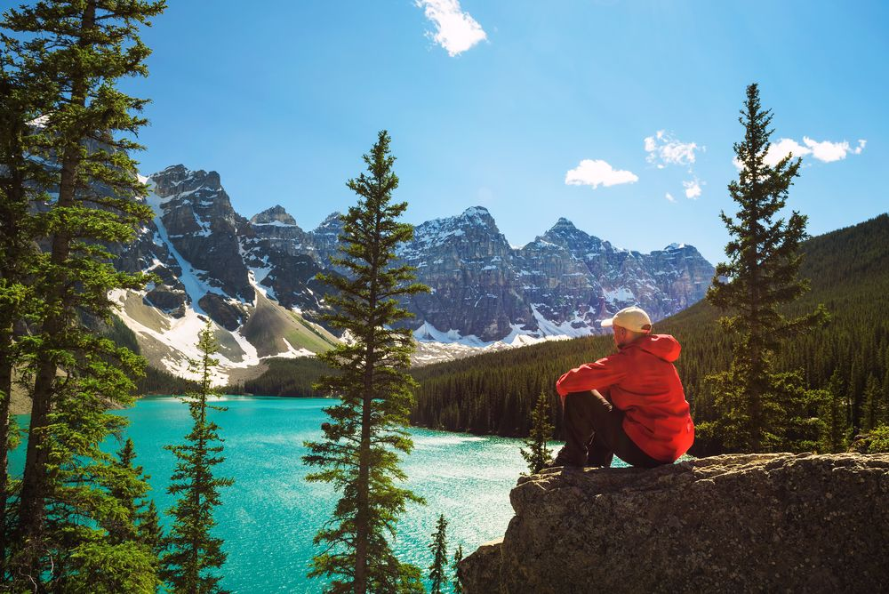 Hiker enjoying the view of Moraine lake in Banff National Park, Alberta, Canada, with snow-covered peaks of Canadian Rocky Mountains in the background
